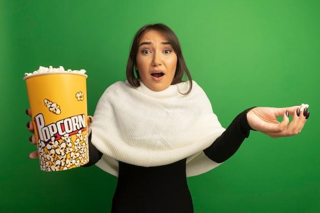 Jonge vrouw met witte sjaal die emmer met popcorn toont die verward schouders ophaalt