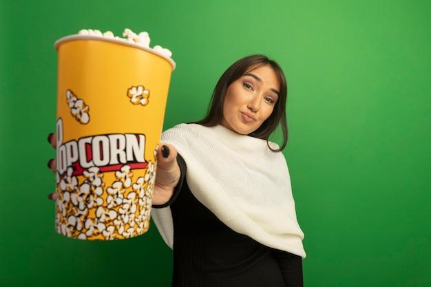 Jonge vrouw met witte sjaal die emmer met popcorn zelfverzekerd glimlachen tonen