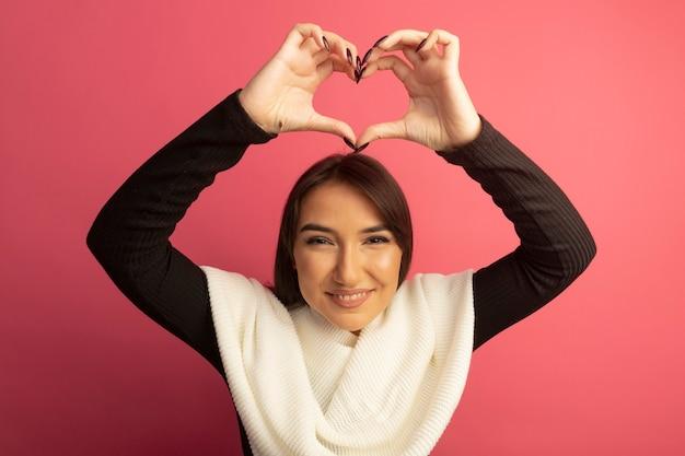 Jonge vrouw met witte sjaal die hartgebaar met vingers boven het hoofd vrolijk glimlachen maken