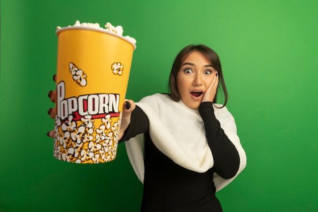 Jonge vrouw met witte sjaal die verbaasd en verrast emmer met popcorn toont