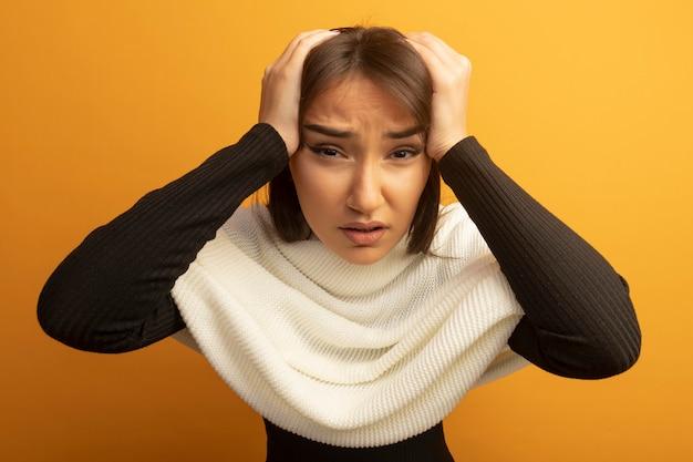 Jonge vrouw met witte sjaal die voor vergissing met handen op haar hoofd wordt verward