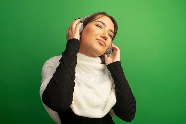 Jonge vrouw met witte sjaal en koptelefoon die van haar favoriete muziek geniet
