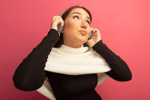 Jonge vrouw met witte sjaal en koptelefoon opzoeken gelukkig en positief genieten van haar favoriete muziek