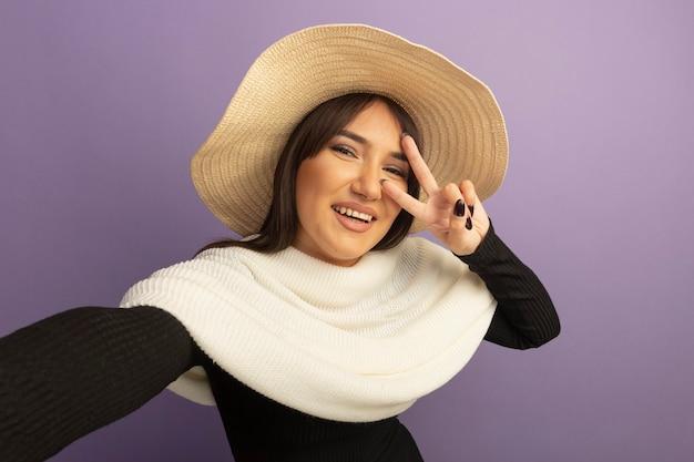 Jonge vrouw met witte sjaal en zomerhoed die met blij gezicht glimlacht dat v-teken toont