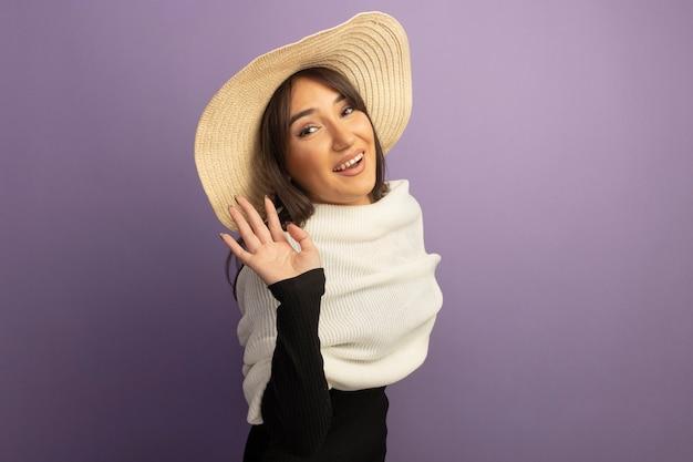 Jonge vrouw met witte sjaal en zomerhoed die vrolijk met hand glimlachen zwaaien
