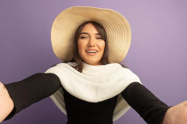 Jonge vrouw met witte sjaal en zomerhoed verwelkomend gebaar met handen gelukkig en positief maken