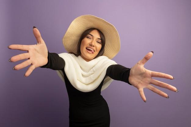 Jonge vrouw met witte sjaal en zomerhoed wijd openende handen die gastvrije gebaar gelukkig en vrolijk maken