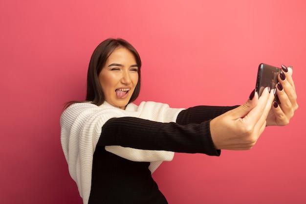 Jonge vrouw met witte sjaal met behulp van smartphone doet selfie lachend met blij gezicht tong uitsteekt