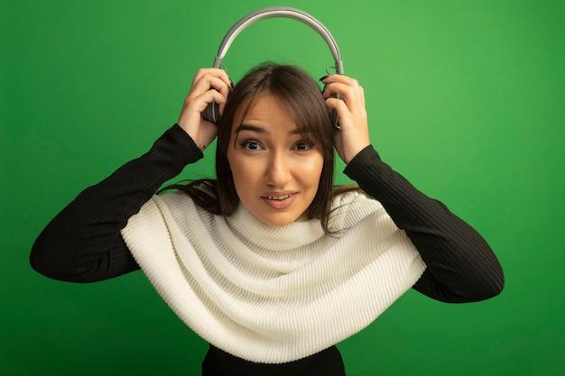 Jonge vrouw met witte sjaal met koptelefoon boven haar hoofd glimlachend zelfverzekerd