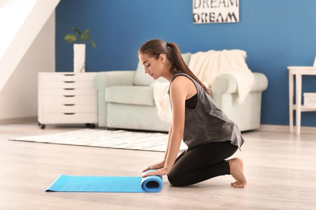 Jonge vrouw met yogamat binnenshuis