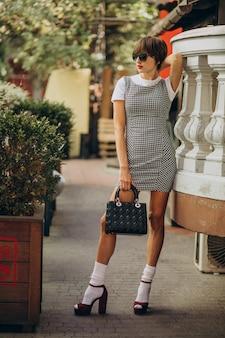 Jonge vrouw met zak buiten de straat