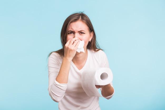 Jonge vrouw met zakdoek. het zieke geïsoleerde meisje heeft een loopneus