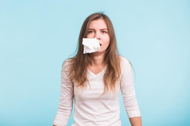 Jonge vrouw met zakdoek. ziek geïsoleerd meisje heeft loopneus op blauwe achtergrond