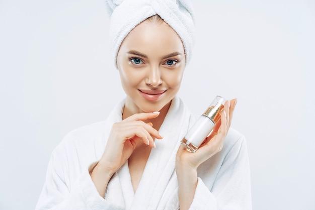 Jonge vrouw met zelfverzekerde uitdrukking, gezonde schone, gladde huid, goed verzorgde teint, houdt fles lotion of gel vast, raakt kaaklijn, gekleed in badjas.