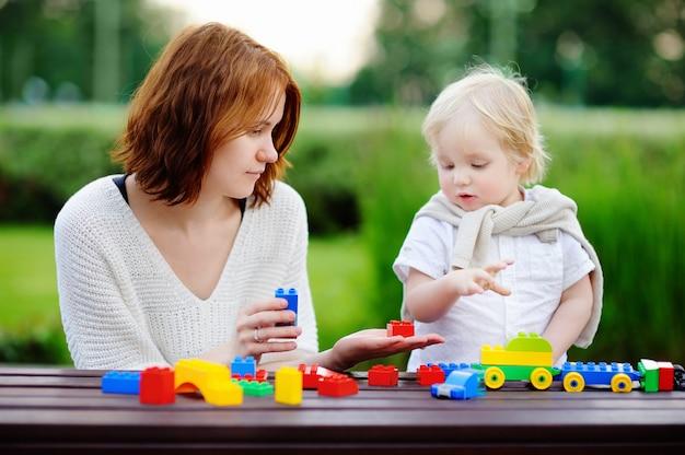Jonge vrouw met zijn peuterzoon het spelen met kleurrijke plastic blokken