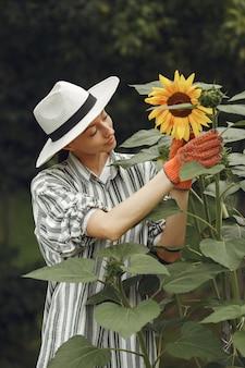 Jonge vrouw met zonnebloemen. dame in een hoed. meisje in een tuin.