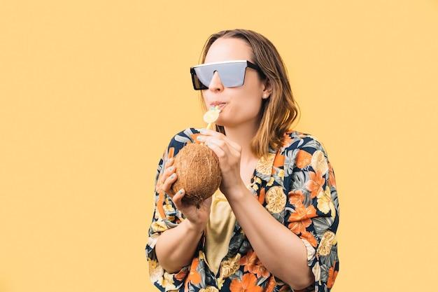 Jonge vrouw met zonnebril en gebloemd hemd die kokosnoot drinkt met plastic rietje op gele achtergrond