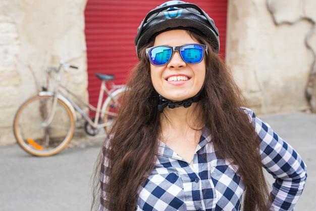 Jonge vrouw met zonnebril en helm in straat op zonnige dag