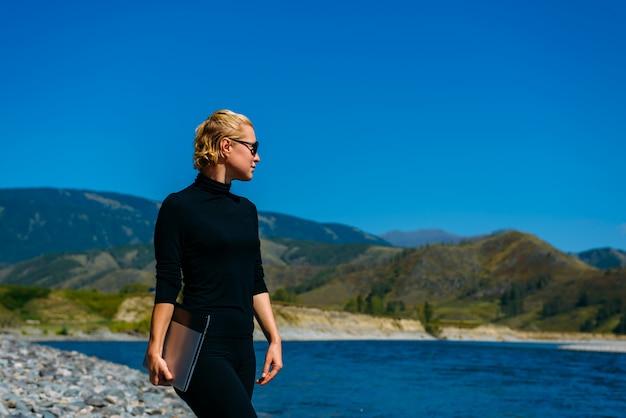 Jonge vrouw met zonnebril naast bergrivier