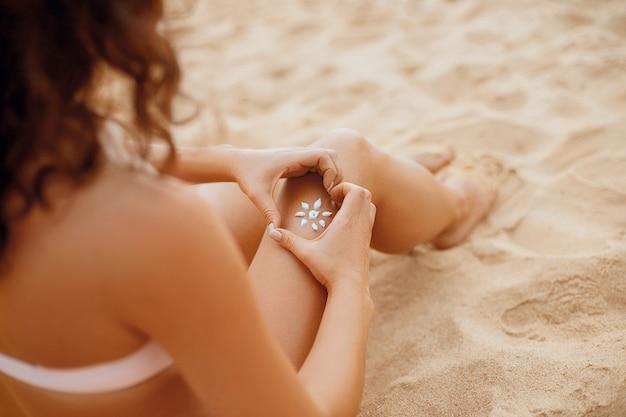 Jonge vrouw met zonvorm op het been. zonnebrandcrème op haar gladde gebruinde benen