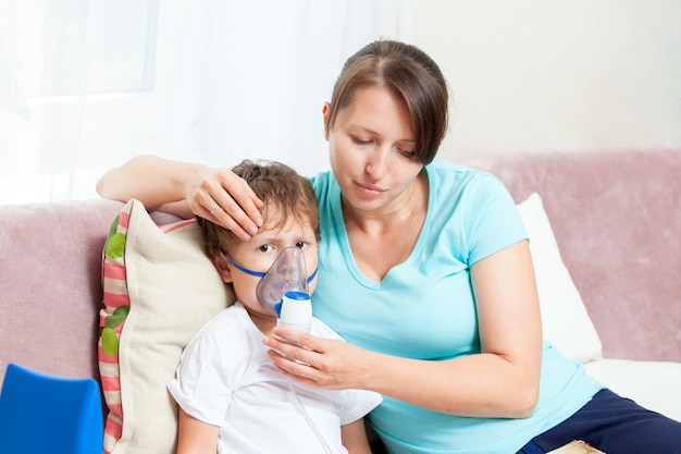 Jonge vrouw met zoon die inhalatie met een verstuiver thuis doet en een boek leest