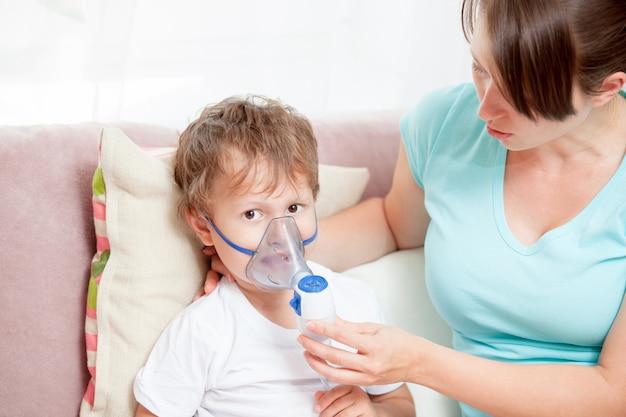 Jonge vrouw met zoon die inhalatie met een verstuiver thuis doet