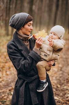 Jonge vrouw met zoontje wandelen in herfst park