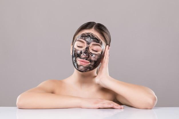 Jonge vrouw met zuiverend zwart masker op haar gezicht dat op witte muur wordt geïsoleerd