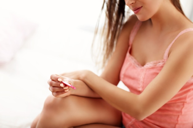 Jonge vrouw met zwangerschapstest in de ochtend