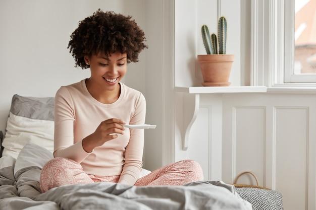 Jonge vrouw met zwangerschapstest thuis poseren