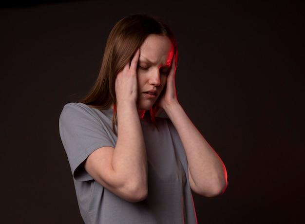 Jonge vrouw met zware scherpe hoofdpijn, die haar slapen vasthoudt met pijn en pijn.