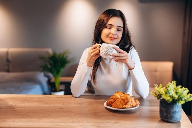 Jonge vrouw met zwart glanzend haar koffie drinken tijdens het ontbijt. indoor portret van schattige brunette meisje croissant eten en genieten van thee in de ochtend.