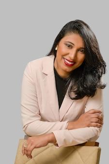 Jonge vrouw met zwart haar met een mooie glimlach die een beige blazer draagt, uitvoerende zakenvrouw