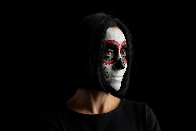 Jonge vrouw met zwart kort haar in witte make-up suiker hoofd naar de dag van de doden