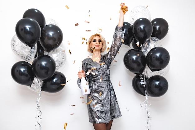 Jonge vrouw met zwarte en zilveren ballonnen