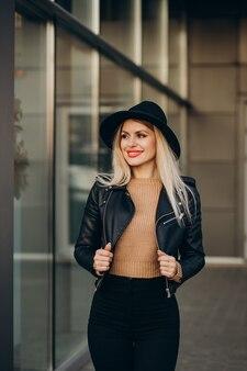Jonge vrouw met zwarte hoed die buiten de straat loopt