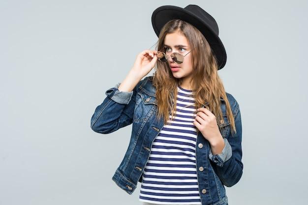 Jonge vrouw met zwarte hoed en zonnebril die op witte achtergrond wordt geïsoleerd