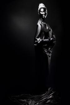 Jonge vrouw met zwarte schmink op een zwarte achtergrond