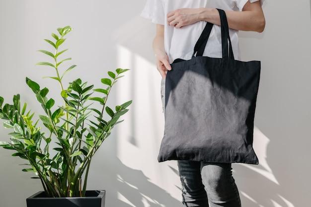 Jonge vrouw met zwarte textiel eco tas tegen witte muur.