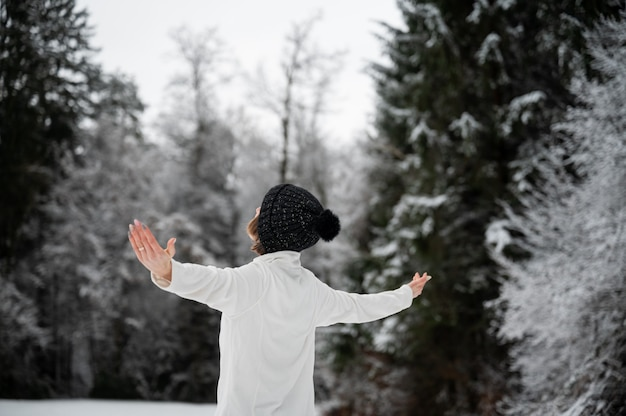 Jonge vrouw met zwarte winter hoed staande in de prachtige besneeuwde natuur met haar armen wijd verspreid.