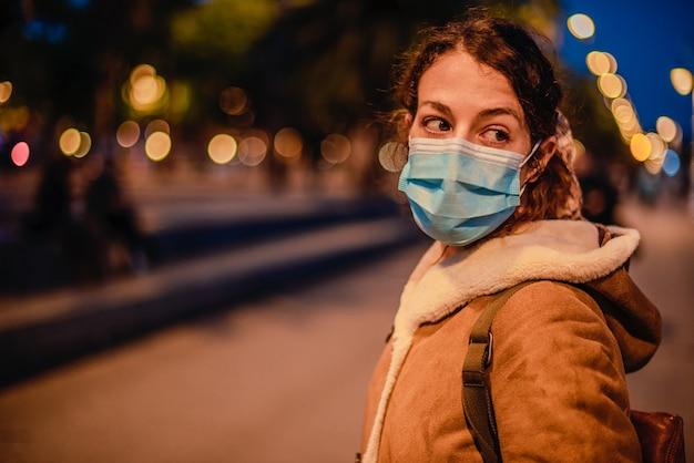 Jonge vrouw midden op straat met een beschermend gezichtsmasker om verspreiding van het virus sars-cov-2 te voorkomen