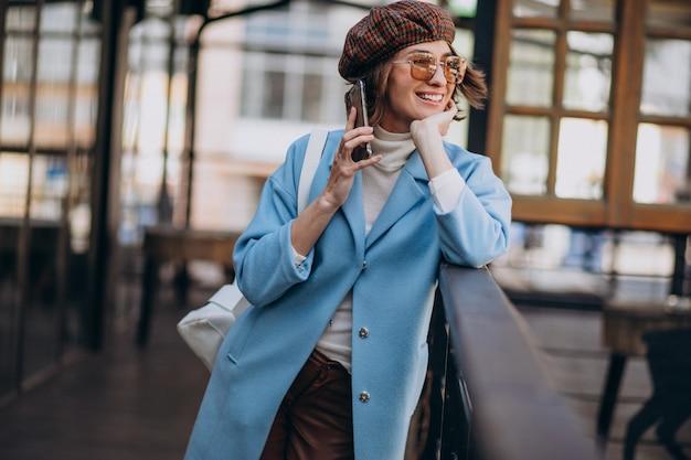 Jonge vrouw model in blauwe jas door het café, met behulp van de telefoon