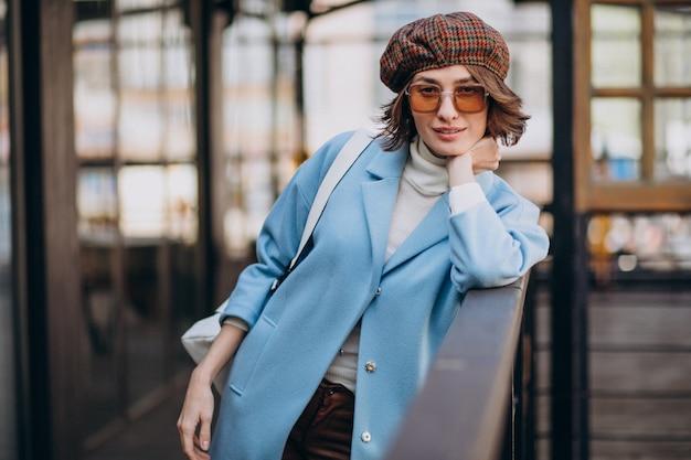 Jonge vrouw model in blauwe jas door het café