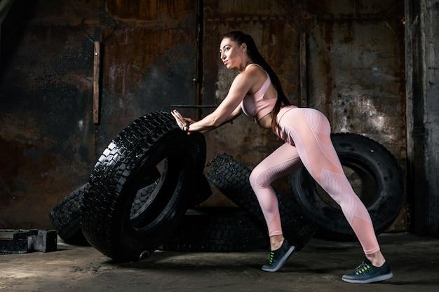 Jonge vrouw model in een sportieve korte top en gym legging poseren en duwen de band in een oude garage