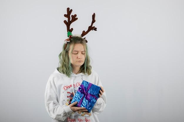 Jonge vrouw model in herten hoorns masker met een cadeautje.