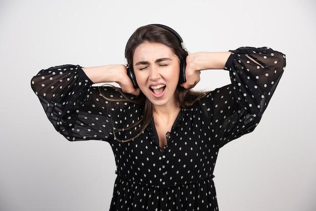Jonge vrouw model luisteren muziek in hoofdtelefoons