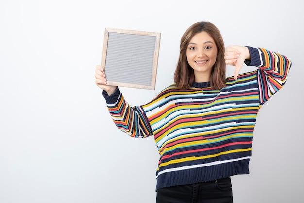 Jonge vrouw model met een frame met een duim naar beneden.