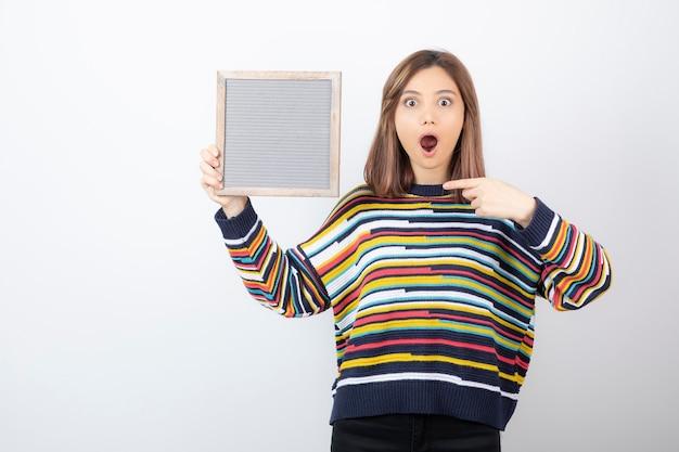Jonge vrouw model permanent en wijzend op een frame.