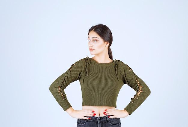 Jonge vrouw model permanent met haar handen op haar heupen en wegkijken.