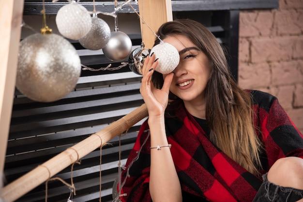 Jonge vrouw model poseren met geruite plaid in de buurt van kerstballen.
